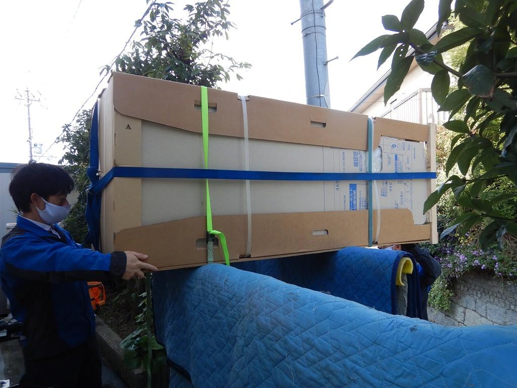 エコキュートを塀の上を運搬